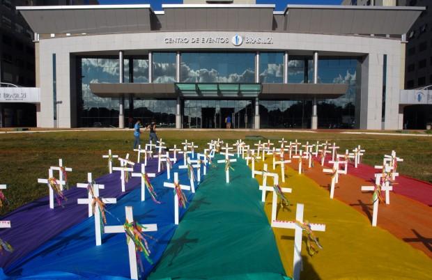 Cruzes sobre a bandeira da diversidade, representando as vítimas de violência transfóbica e homofóbica.